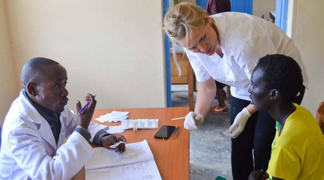 On a volunteer opportunity for college graduates, a recent graduate assists a local doctor during a medical outreach in Kenya.
